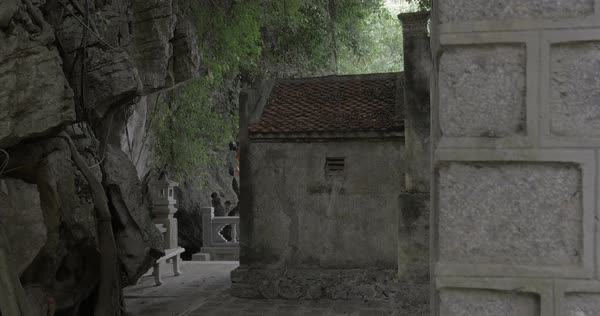 Aged stone house by the rock with banyan tree roots, Vietnam Royalty-free stock video