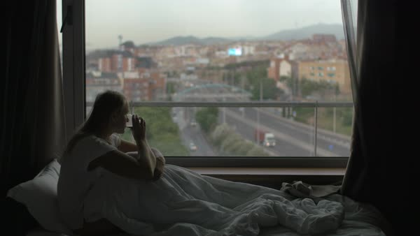 Woman sitting under blanket on bed, drinking tea and looking at the city through the window Royalty-free stock video