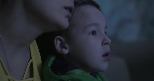 Close-up shot of mother and son watching interesting movie or cartoon at the theatre. Boy staring at the screen, mom talking to him Royalty-free stock video