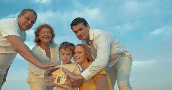 Steadicam shot of big family with small wooden house. Boy holding it and they all protecting it with hands. Family hearth or insurance concept Royalty-free stock video