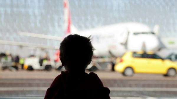 Little boy watching planes at the airport standing in silhouette with his back to the camera at a large window overlooking the tarmac Royalty-free stock video