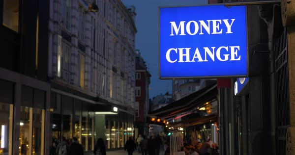 Blue and white Money Change banner hanging in the street with unidentified people walking along it at night Royalty-free stock video