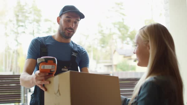 Homeowner opens the door to delivery man and receives parcel after signing on delivery device Royalty-free stock video