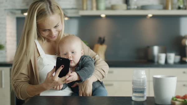 Young mother holds her baby while being in the kitchen Royalty-free stock video