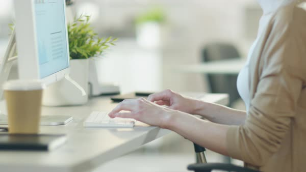 Close-up of woman's hands typing on a keyboard using her personal computer in very lightsome modern environment. Royalty-free stock video