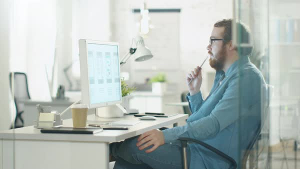 Focused creative man thinks while sitting at his workplace desk. he holds pencil and looks at desktop computer screen. Royalty-free stock video