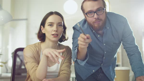 Portrait shot of a man and a woman discussing work looking streight at the camera. they are in the brightly lit modern office. Royalty-free stock video