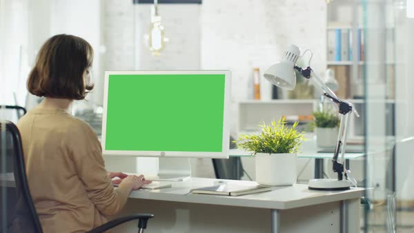 Creative young girl works on her desktop computer. her office/ creative studio is brightly lit. computer screen is green mock-up. Royalty-free stock video