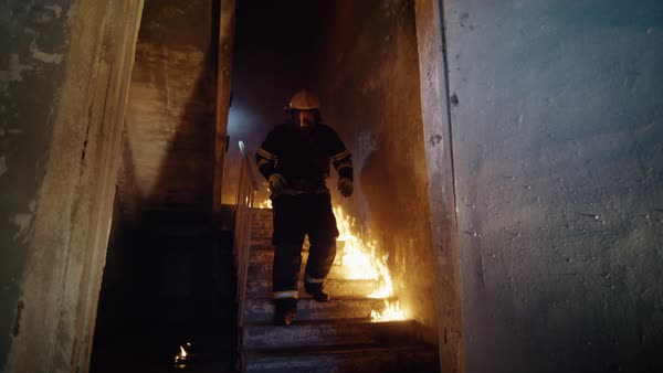 Fully equipped firefighter runs down on burning stairs Royalty-free stock video