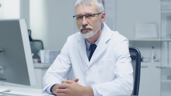 Experienced gray haired senior medical practitioner looking into camera. Portrait shot in modern and light office. Royalty-free stock video