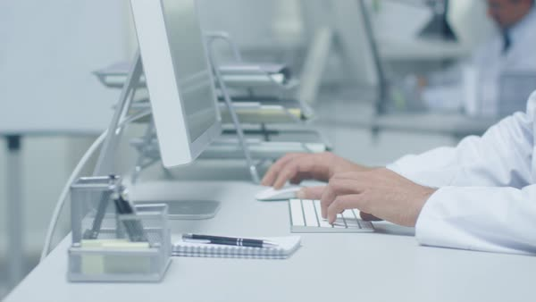 Close-up of medical practitioner's hands typing on a keyboard working on his desktop computer. In background assistant is working. Royalty-free stock video
