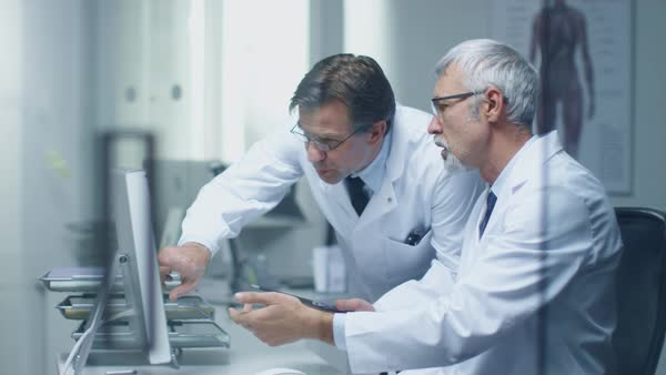 Two senior medical practitioners discussing medical issues over desktop computer. One of them hold tablet computer. Office is modern and bright. Royalty-free stock video