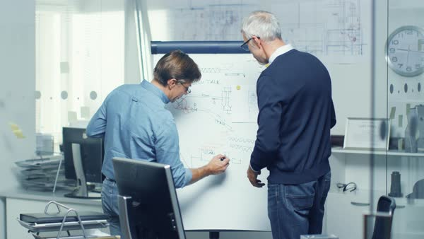 In architectural engineering office two senior engineers working with drafts on a whiteboard. Their office looks minimalistic and modern. Royalty-free stock video