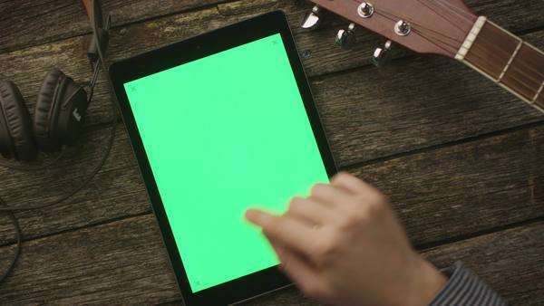 Musician using tablet pc with green screen in portrait mode, top view. Royalty-free stock video