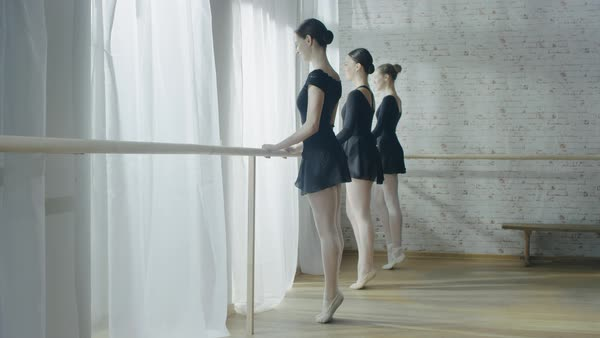 Three young and beautiful ballerinas stretching legs and exercising at ballet barre Royalty-free stock video