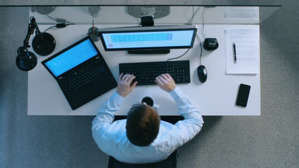 Top view of IT specialist working with spreadsheets and documents on his laptop and personal computer simultaneously. Stack of signed papers on his desk. Royalty-free stock video