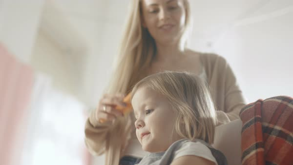 Sweet young mother brushes hair of her cute little blonde daughter. Royalty-free stock video