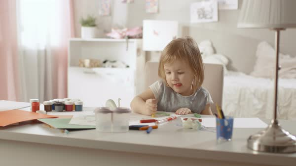 Cute little girl sits at her table and draws with crayons. Her room is pink, pretty drawings hanging on the walls, many toys lying around. Royalty-free stock video