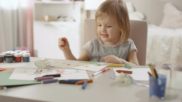 Cute little girl sits at her table and draws with crayons. Happy with the results she smiles. Her room is pink, pretty drawings hanging on the walls, many toys lying around. Royalty-free stock video