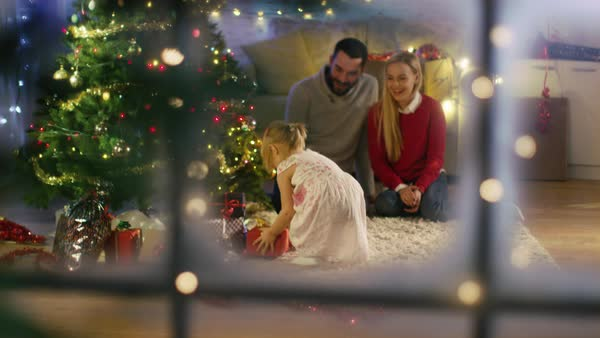 Looking Through Snowy Window. Happy Father, Mother and Daughter Sitting Under Christmas Tree. Daughter Gives a Gift to Her Mother. Royalty-free stock video