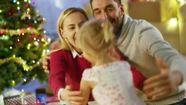 On Christmas Eve Happy Parents Hug Their Little Cute Daughter Under Christmas Tree. Royalty-free stock video