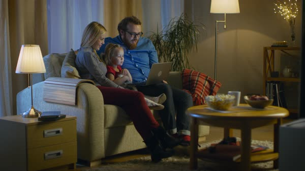 Long shot of a father, mother and little girl watching tv. They sit on a sofa in their cozy living room, father holds laptop on his knees. It's evening. Royalty-free stock video