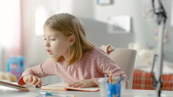 Smart little girl does homework in her room. Royalty-free stock video