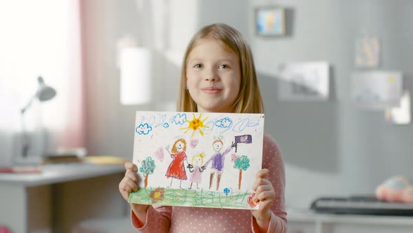 Cute young girl shows fun drawing of her happy family. Mother, father and her holding hands on the drawing. Royalty-free stock video