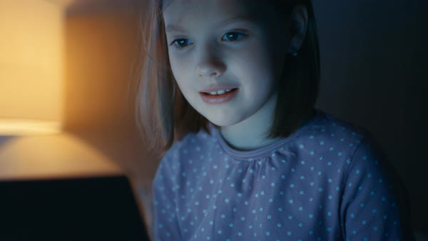 Cute little girl sits with tablet computer on her bed at night. Royalty-free stock video