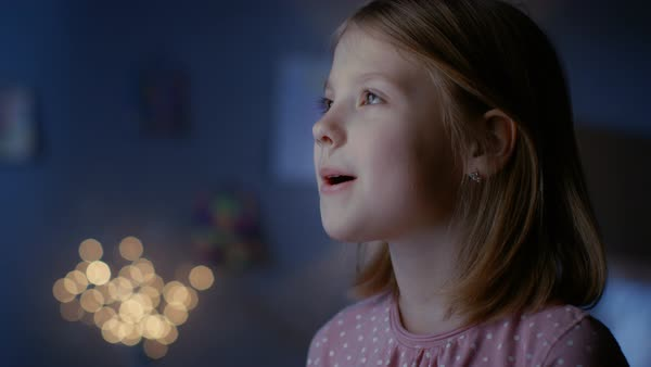 Girl filled with wonder happily looks out of the window. Royalty-free stock video