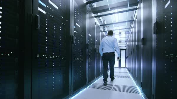 Elevating shot in data center. Starts from underground then elevates to the glass ceiling. Rows of server racks in this data server are visible. IT engingeer working there. Royalty-free stock video