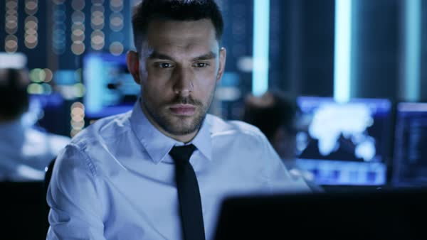 Close-up of a professional technical controller sitting at his desk with multiple displays before him Royalty-free stock video