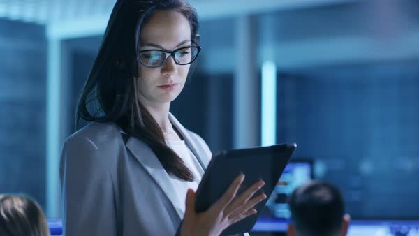 Young female government employee wearing glasses uses tablet in system control center Royalty-free stock video