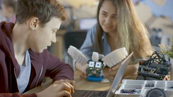 Girl and boy program fully functional robot with laptop for their science/ robotic/ engineering class at school Royalty-free stock video