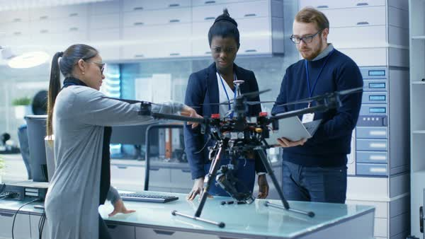 Multi ethnic team of young female and male engineers working on modern drone prototype Royalty-free stock video