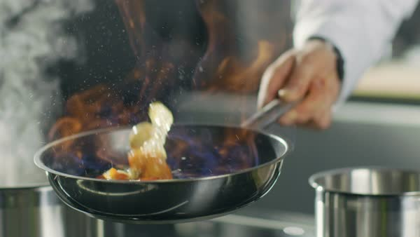 Close-up of a Chef Preparing Flambe Style Dish on a Pan. Oil and Alcohol Ignite with Open Flames. Royalty-free stock video
