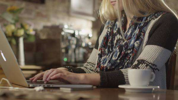 Pretty girl typing on laptop in coffee shop. Royalty-free stock video
