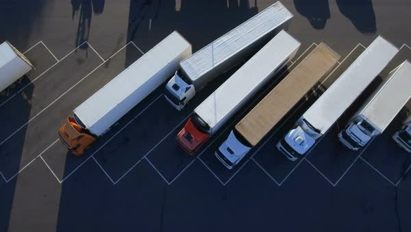 Aerial top view of white semi truck with cargo trailer parking with other vehicles on special parking lot Royalty-free stock video