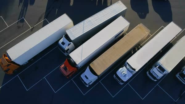 Aerial top view of white semi truck with cargo trailer parking with other trucks on special parking lot Royalty-free stock video