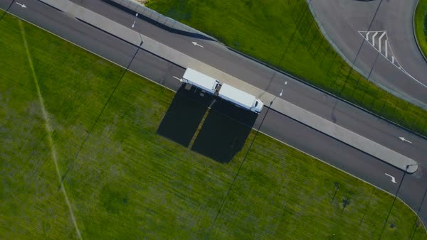 Aerial top view of white truck with cargo semi trailer moving on the road in the direction of loading warehouse/ industrial area Royalty-free stock video