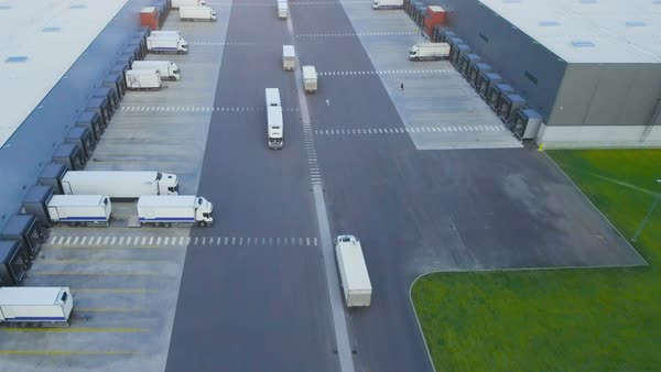 Aerial shot of truck with attached semi trailer leaving industrial warehouse/ storage building/ loading area where many trucks are loading/ unloading merchandise Royalty-free stock video