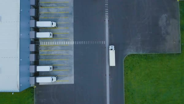 Zoom out aerial shot of industrial warehouse/ storage building/ loading area where many trucks are loading/ unloading merchandise Royalty-free stock video