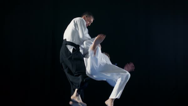 Martial Arts Master Wearing Hakamas Teaches Young Student Aikido Technique. Shot Isolated on Black Background and in Slow Motion.  Royalty-free stock video