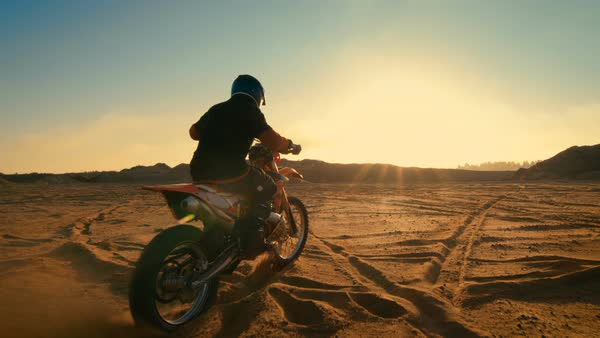 Following shot of the professional motocross driver riding on his FMX motorcycle on the extreme off-road terrain track Royalty-free stock video