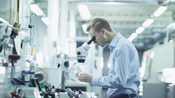 Engineer inspects detail quality under microscope on factory Royalty-free stock video