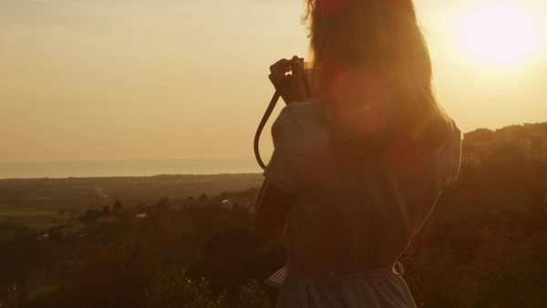 Girl taking photos of nature with old film camera at sunset time Royalty-free stock video