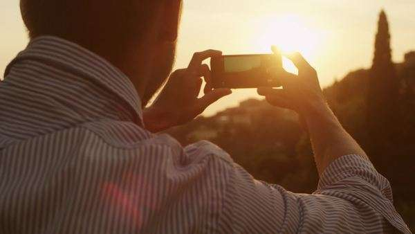 Man taking photos of nature with a phone at sunset time Royalty-free stock video