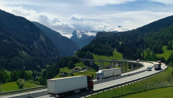 Aerial shot of the road with heavy traffic stretching into the valley with enormous mountains with snow peaks in the background Royalty-free stock video