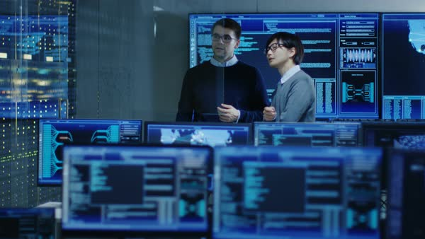 In the System Control Room Project Manage and IT Engineer Have Discussion, they're surrounded by Multiple Monitors with Graphics. They Work in a Data Center on Data Mining, AI and Neural Networking.  Royalty-free stock video