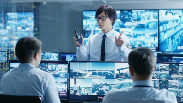 In the Security Control Room Chief Surveillance Officer Holds a Meeting for Two Staff Members. Multiple Screens Show that They Guard Object of Big Importance.  Royalty-free stock video